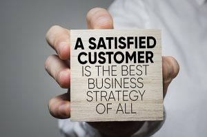 NJ ITM Service, Businessman holding block with statement about satisfied customers, NJ ITM service equals happier clients