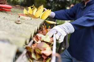 Gutter cleaning in Marlboro, leaves shown clogging gutter being cleaned out by a gloved hand
