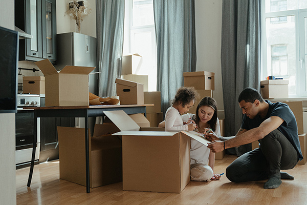 Lavallette real estate agent warns against dangers of not staying organized. Picture shows family of 3 surrounded by boxes in different states of being finished and child is inside of a box.
